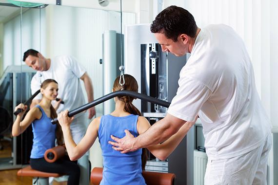 упражняване на пациент във фитнес  с помощта на терапевт