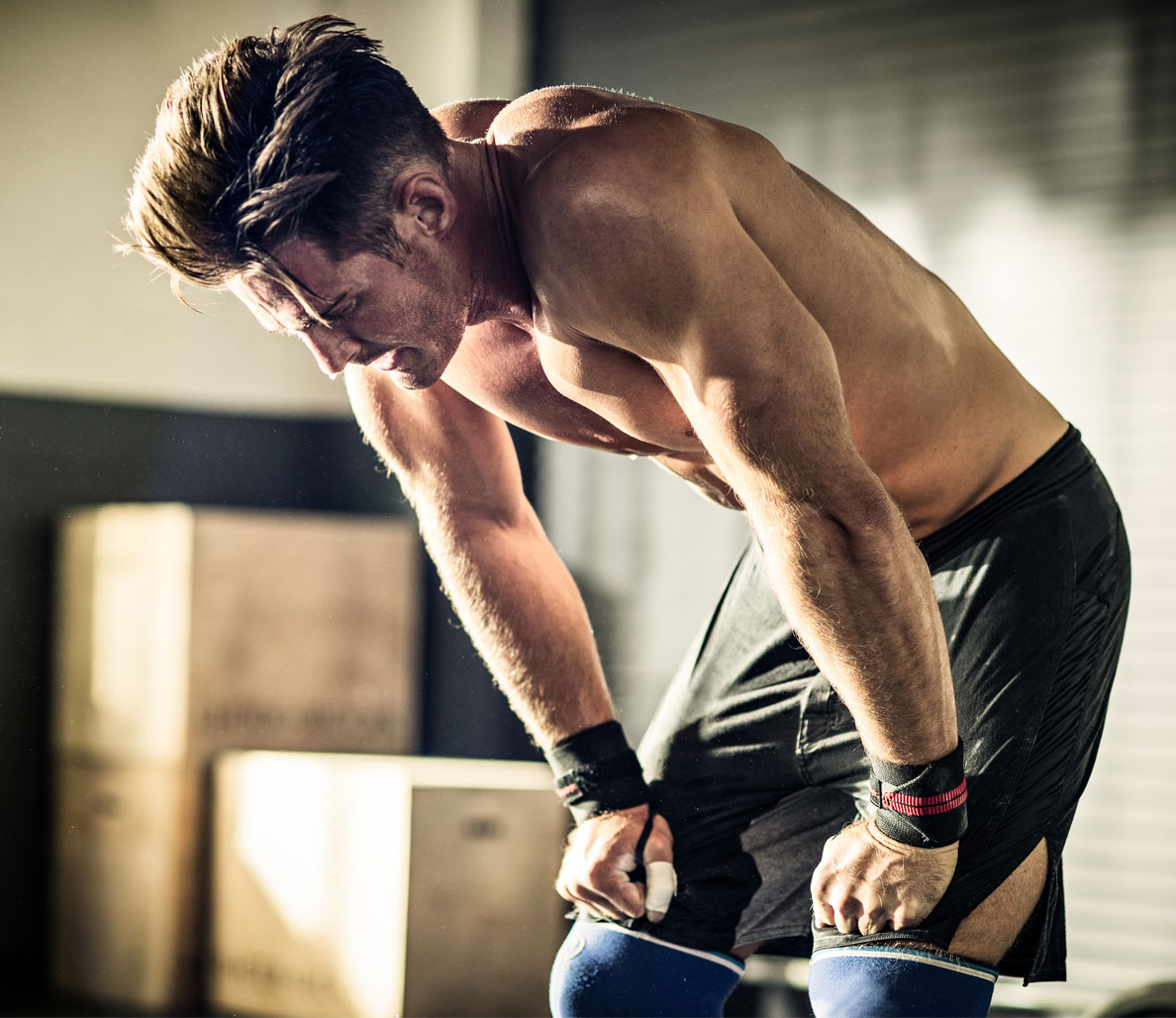 мъж в спортен екип се подпира отчаяно на коленете си