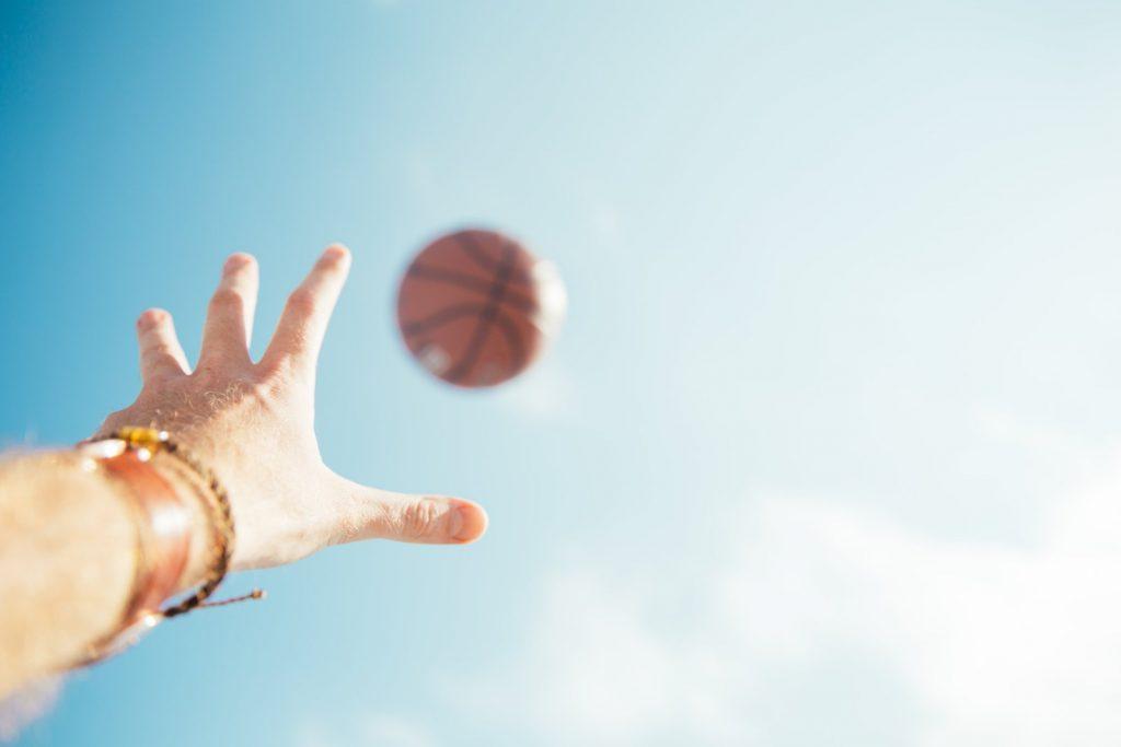 ръка протегната към баскетболна топка