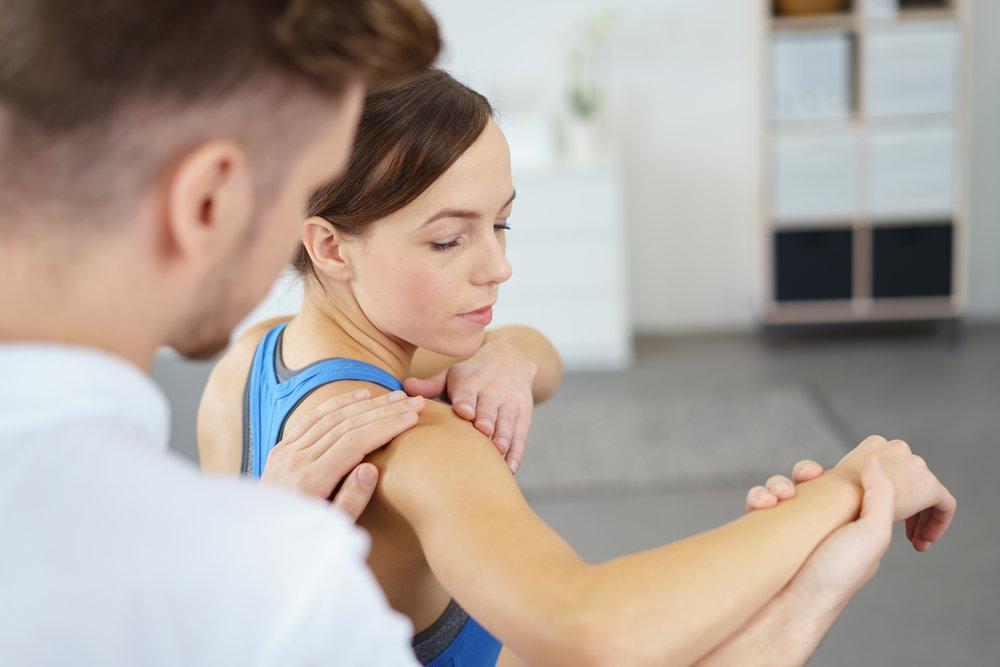 терапевт раздвижва ръката на пациентка